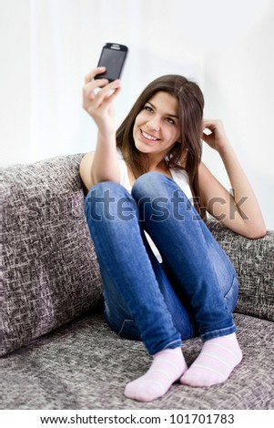 cute teenage girl taking picture of herself, smiling and looking in phone - stock photo