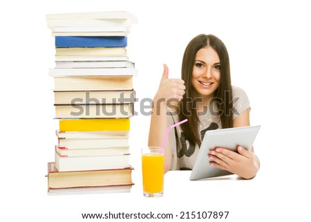 Cute teenage girl with digital tablet and pile of books gesturing thumbs up smiling looking at camera isolated on white background. - stock photo