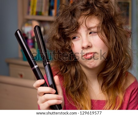 Cute teenage girl with messy hair and flatiron straightener - stock photo