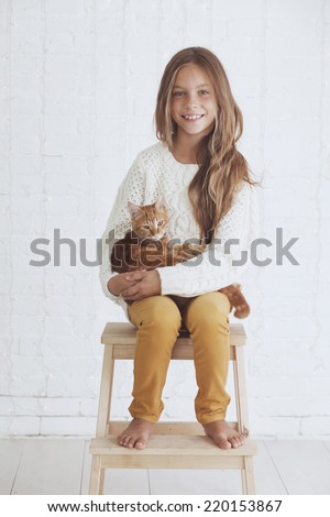 Cute teenage girl 8-9 years old wearing knit trendy winter clothes holding her ginger cat posing over white brick wall - stock photo