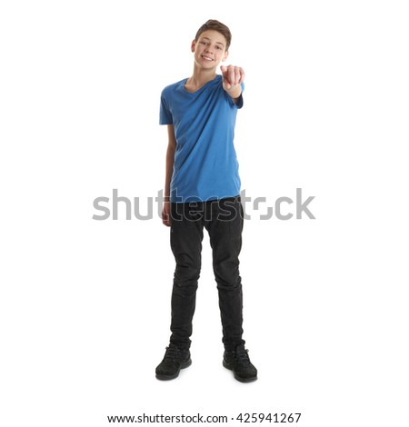 Cute teenager boy in blue T-shirt standing and poinitng forward over white isolated background full body - stock photo