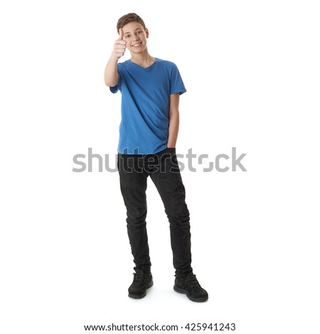 Cute teenager boy in blue T-shirt standing and showing thumb up sign over white isolated background full body - stock photo