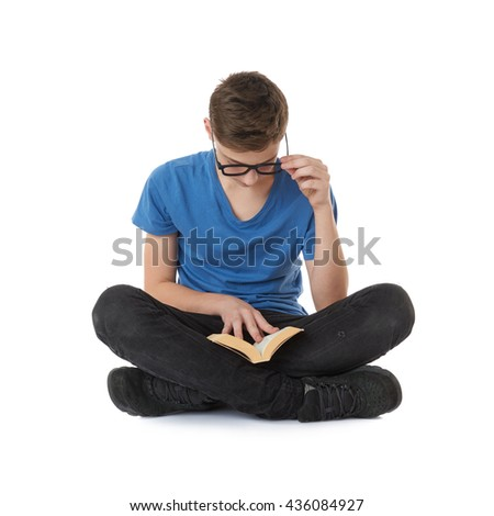 Cute teenager boy with book in blue T-shirt, glasses and lotus posture over white isolated background - stock photo