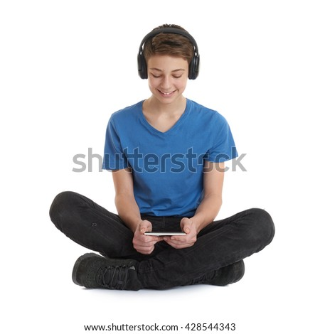 Cute teenager boy with smart phone in hands in blue T-shirt, headphones and lotus posture over white isolated background - stock photo