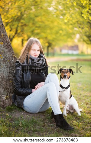 Cute Teenager girl with her Dog in beautiful park.  - stock photo
