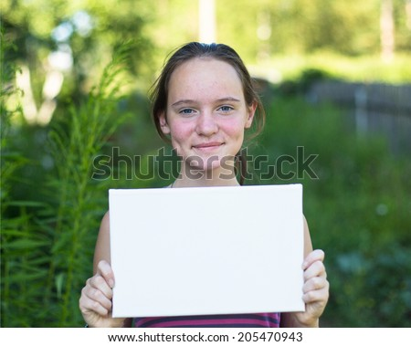 Cute  teengirl holding clean white sheet paper, outdoors (banner for your message) - stock photo