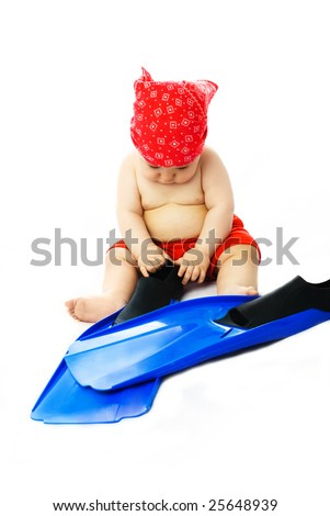 cute ten months old baby sitting on the floor and putting on blue flippers - stock photo