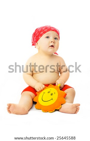 cute ten months old baby wearing red beach clothes with a toy Sun in his hands - stock photo