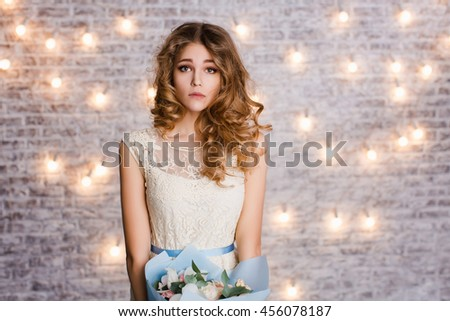 Cute tender slim girl with blond curly hair standing in a studio with white background with flashlights. She smiles widely and looks puzzled. She holds a blue bouquet of flowers. - stock photo