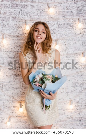 Cute tender slim girl with blond curly hair standing in a studio with white background with flashlights. She smiles and looks sweet. She has her arm near her chin and holds a blue bouquet of flowers. - stock photo