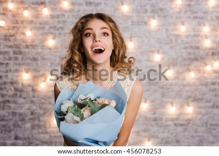 Cute tender slim girl with blond curly hair standing in a studio with white background with flashlights. She smiles widely and looks surprised. She holds a blue bouquet of flowers. - stock photo