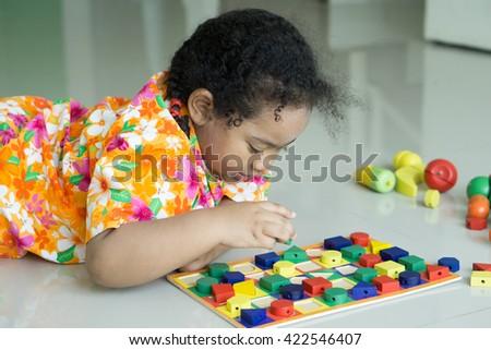 Cute Thai-Nigeria child play the wooden block on the floor. - stock photo