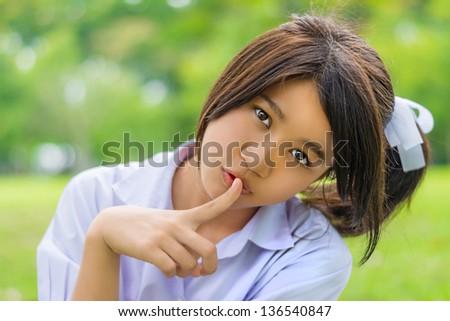 Cute Thai schoolgirl doing hush gesture in green bokeh background. She looks a bit naughty - stock photo