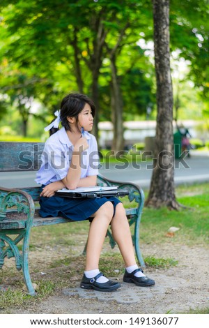Cute Thai schoolgirl is sitting and studying on a bench. Sometimes she olet her mind flow with imagination. - stock photo
