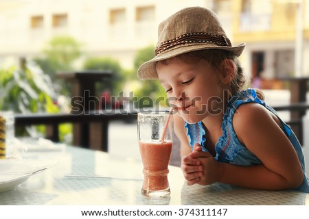 Cute thinking kid girl drinking tasty juice in street restaurant - stock photo