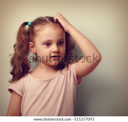 Cute thinking worried kid girl scratching the head and looking on empty copy space. Vintage closeup portrait - stock photo
