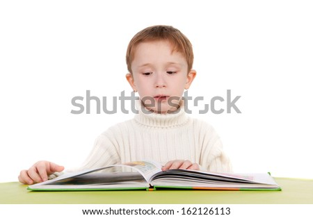 cute thoughtful boy reading a book - stock photo
