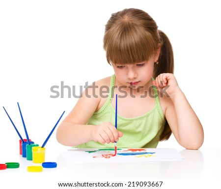 Cute thoughtful child play with paints while sitting at table, isolated over white - stock photo