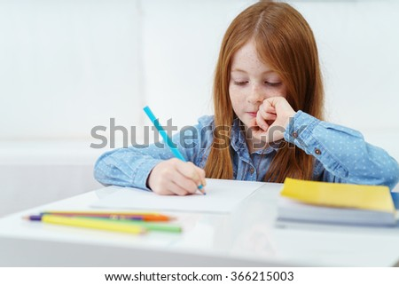 Cute thoughtful little girl sitting at a table at home doing homework for school as she writes or draws with a colored pencil - stock photo