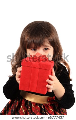 Cute three year old little girl dressed up in a fancy dress hiding behind a red giftbox on a white background - stock photo