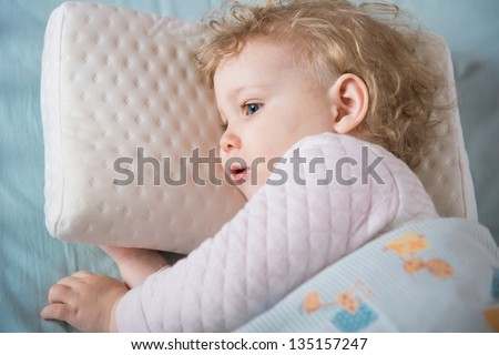 Cute tired girl lying in bed on pillow - stock photo