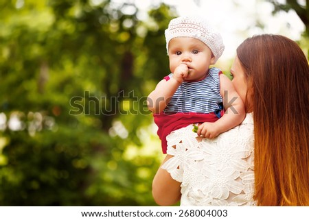 Cute Toddler Baby Girl sitting on Mom`s Hands, looking into camera. Relaxing in green summer Park. - stock photo