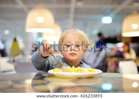 Cute toddler boy eating potatoes in indoors cafe  - stock photo