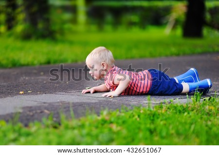 Cute toddler boy fell on park road - stock photo