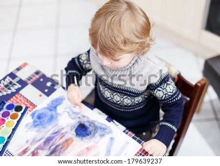Cute toddler boy having fun indoor, painting with different paints colors - stock photo