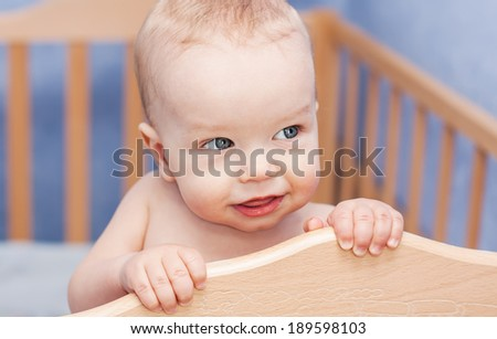 Cute toddler boy peeking out of the cot standing - stock photo