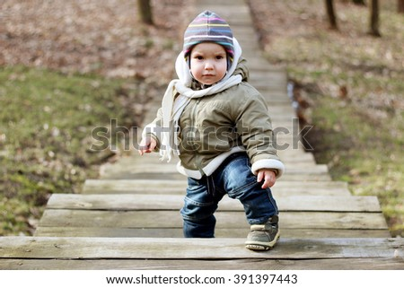 Cute toddler boy walking up stairs in spring park at first sunny spring day, happy family weekend - stock photo