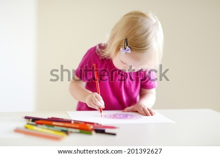 Cute toddler girl drawing a picture with colorful pencils - stock photo