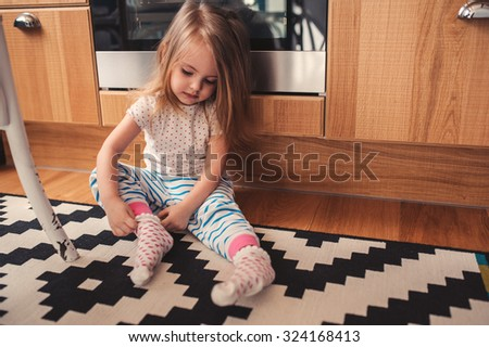 cute toddler girl dressing herself at home, wearing pajama and socks - stock photo