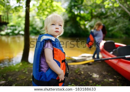 Cute toddler girl getting ready for kayaking with her parent - stock photo