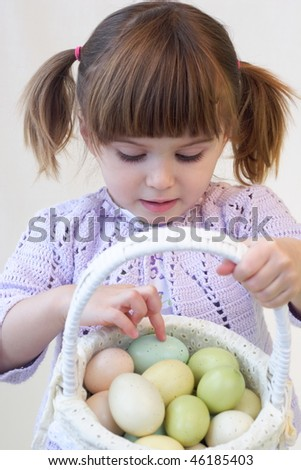 Cute toddler girl holding a basket of Easter eggs - stock photo