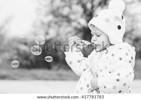 cute toddler girl is blowing soap bubbles - stock photo