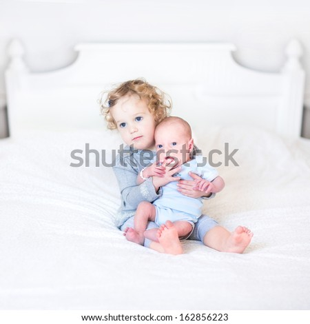 Cute toddler girl playing with her newborn baby brother - stock photo