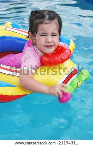 cute toddler girl sitting in plane inflatable in swimming pool - stock photo