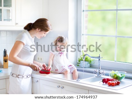 Cute toddler girl with curly hair wearing a white dress helping her mother to cook vegetables in a beautiful sunny kitchen with a big garden view window - stock photo