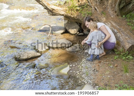 cute toddler girl with her mother in  throwing scree in the stream - stock photo