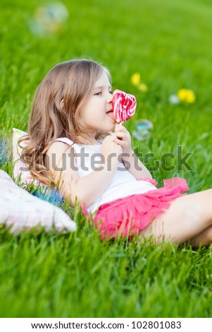 Cute toddler girl with lollipop resting on the grass in summer day - stock photo