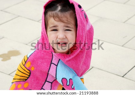 cute toddler girl wrapped in towel with hood after having a  swim - stock photo