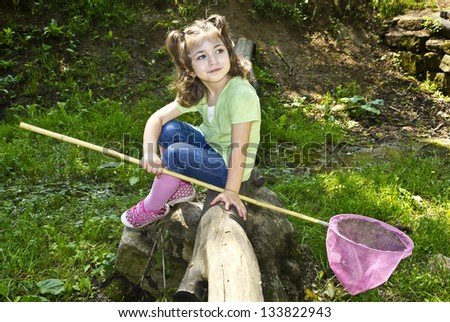 Cute toddler holding a butterfly net - stock photo