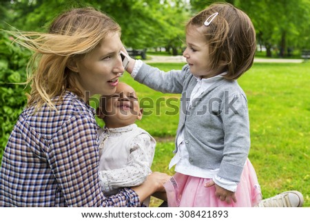 Cute toddler holding a smartphone to mother's ear - stock photo