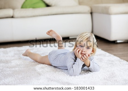 Cute toddler lying on soft carpet at room - stock photo