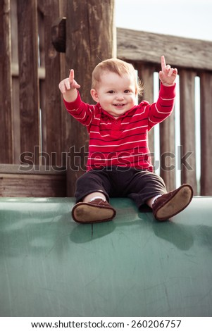 Cute toddler playing slide at playground
