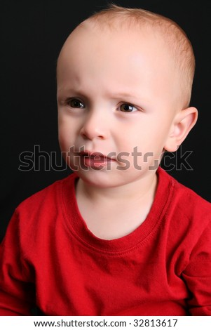 Cute toddler wearing a red shirt with a frown - stock photo