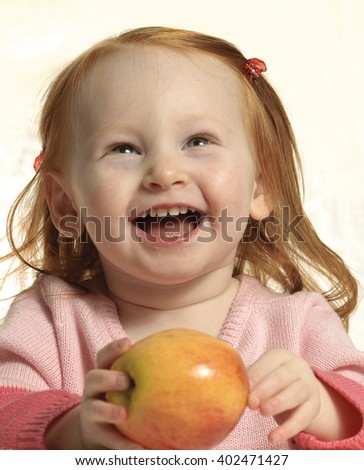 Cute toddler with red hair holding an apple - stock photo