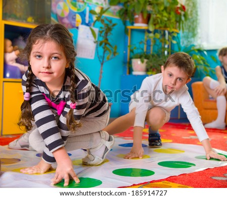 Cute toddlers playing in twister game at kindergarten - stock photo