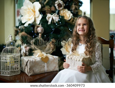 Cute toothless girl rejoices Gifts for Christmas - stock photo
